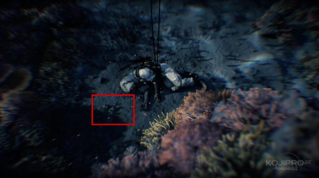 Une poupée de couleur noir gît dans les fonds marins, à gauche de Sam.