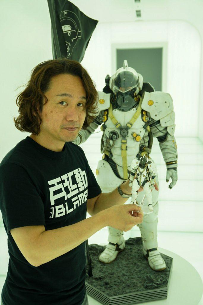 Yoji Shinkawa tenant dans ses mains la figurine Figma de Ludens, devant la statuette de Ludens par Prime 1 Studio,  le 25 mai 2017